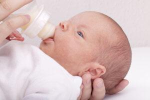 Baby mit Milch aus dem Fläschen ernähren